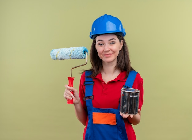 La giovane ragazza sorridente del costruttore con il casco di sicurezza blu tiene il rullo di vernice e la vernice su fondo verde isolato