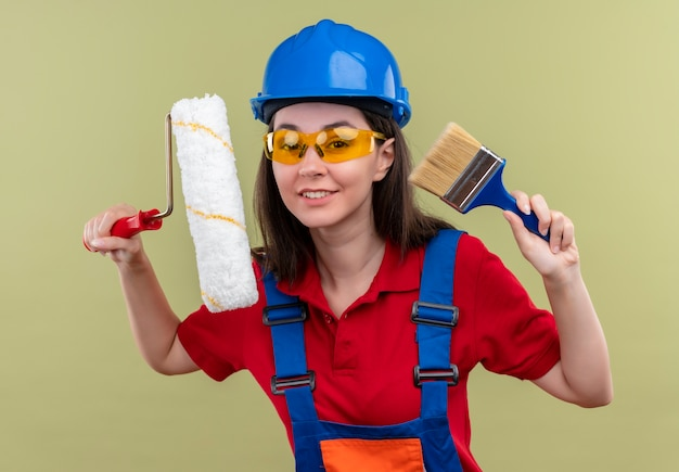 Smiling young builder girl with blue safety helmet and with safety glasses holds paint roller and paint brush on isolated green background