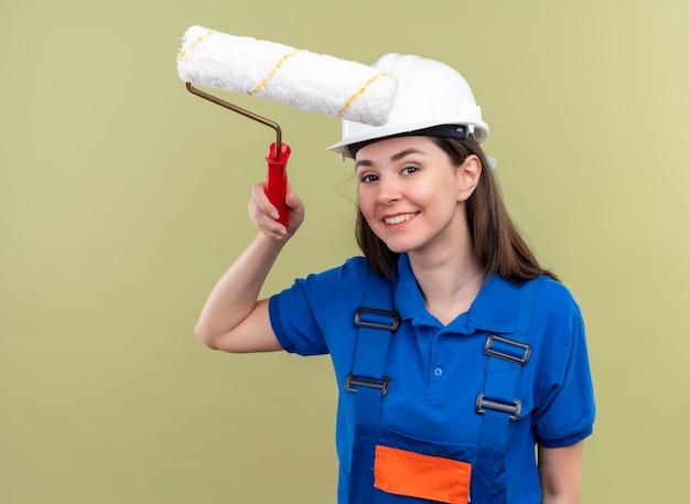 흰색 안전 헬멧 및 파란색 유니폼 웃는 젊은 작성기 소녀 격리 된 녹색 배경에 페인트 롤러를 보유