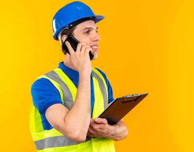 클립보드를 들고 제복을 입은 웃고 있는 젊은 건축업자가 전화로 말한다