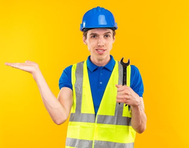 오픈 엔드 렌치를 들고 제복을 입은 웃고 있는 젊은 건축업자가 복사 공간이 있는 노란색 벽에 격리된 쪽에 손을 대고 가리킵니다.