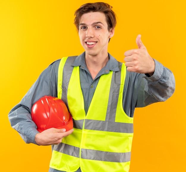 黄色の壁に分離された親指を示す安全ヘルメットを保持している制服を着た若いビルダーの男を笑顔