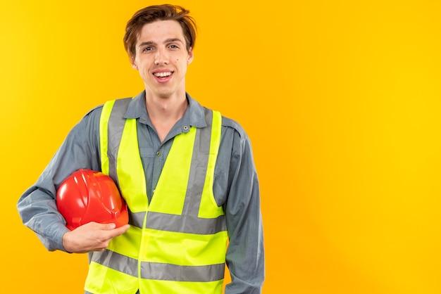 복사 공간이 있는 안전 헬멧을 들고 제복을 입은 웃는 젊은 건축업자