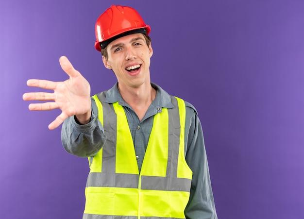 파란 벽에 격리된 5개를 보여주는 제복을 입은 웃고 있는 젊은 건축업자