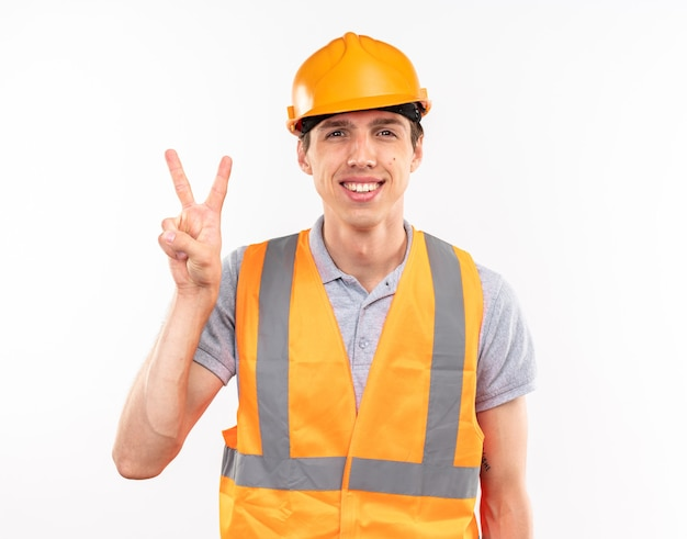 白い壁に分離された平和のジェスチャーを示す制服を着た若いビルダーの男を笑顔