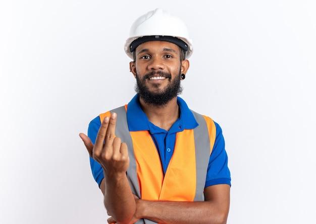 안전 헬멧을 쓴 제복을 입은 웃고 있는 젊은 건축업자가 복사공간이 있는 흰 벽에 손을 얹은 사람을 부른다