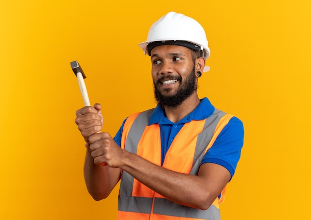 안전 헬멧을 들고 제복을 입은 웃고 있는 젊은 건축업자가 복사 공간이 있는 주황색 벽에 격리된 망치를 보고 있다