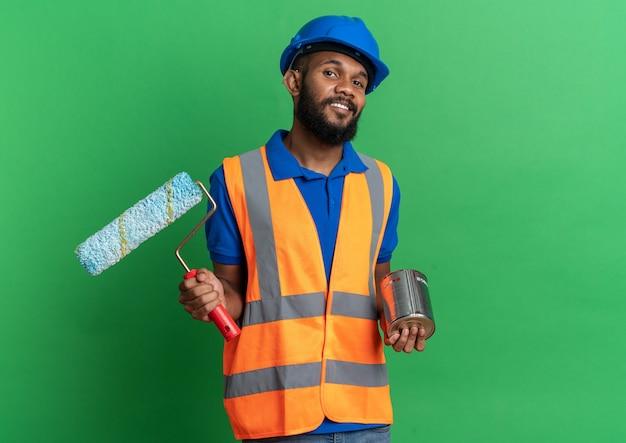 녹색 벽에 복사 공간이 있는 유성 페인트와 페인트 롤러를 들고 안전 헬멧을 쓴 제복을 입은 웃고 있는 젊은 건축업자