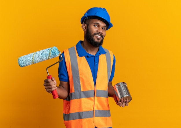 주황색 벽에 복사 공간이 있는 유성 페인트와 페인트 롤러를 들고 안전 헬멧을 쓴 제복을 입은 웃고 있는 젊은 건축업자