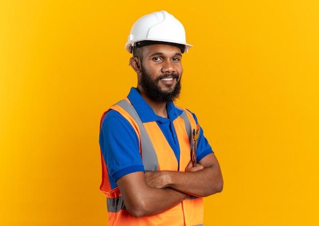 복사 공간이 있는 주황색 벽에 팔짱을 끼고 서 있는 안전 헬멧을 쓴 제복을 입은 웃고 있는 젊은 건축업자