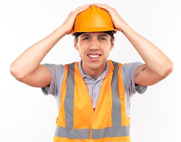 Sorridente giovane costruttore uomo in uniforme ha afferrato la testa isolata sul muro bianco