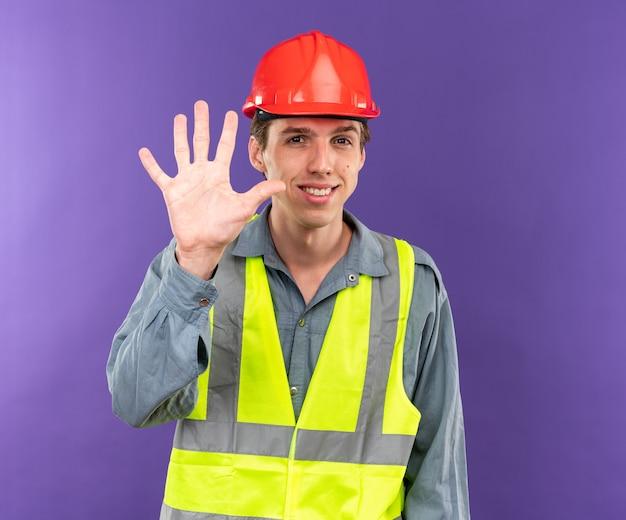 Sorridente giovane costruttore in uniforme che mostra cinque isolati sulla parete blu
