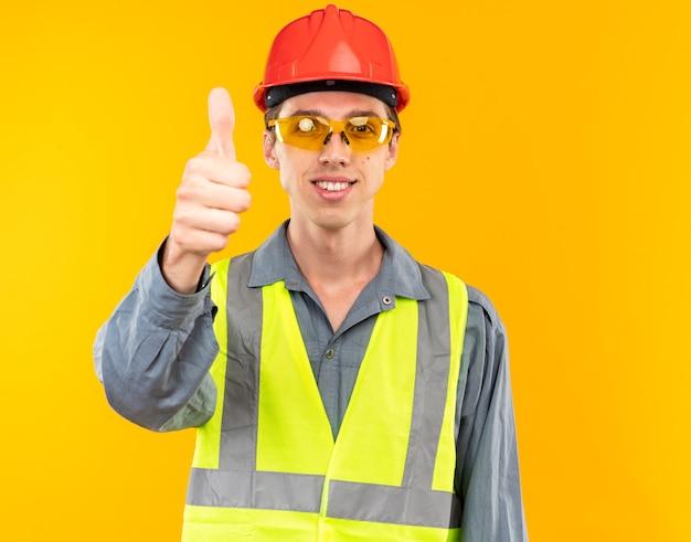 Sorridente giovane costruttore in uniforme con gli occhiali che mostra il pollice in su