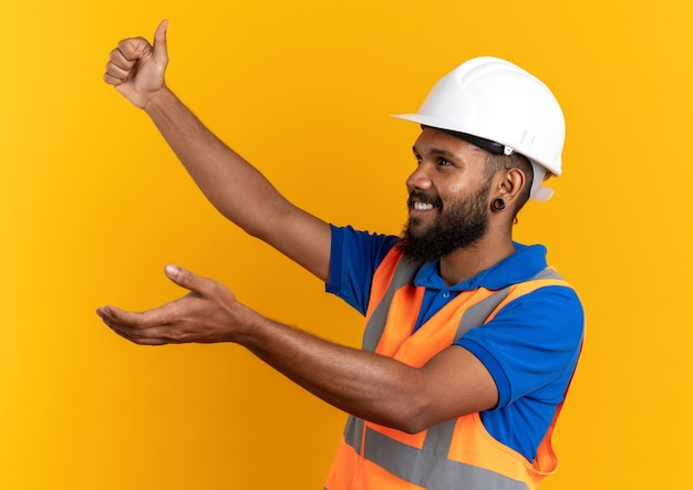 Sorridente giovane costruttore uomo in uniforme con casco di sicurezza sfogliando guardando il lato isolato sulla parete arancione con copia spazio