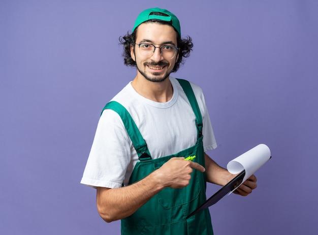 모자를 쓰고 클립보드를 가리키는 유니폼을 입은 웃고 있는 젊은 건축업자