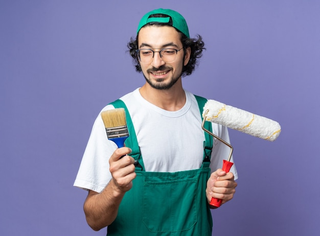Smiling young builder man wearing uniform with cap holding roller brush and looking at paint brush in his hand