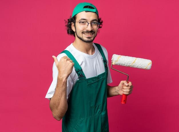 엄지손가락을 보여주는 롤러 브러시를 들고 모자와 유니폼을 입고 웃는 젊은 건축업자 남자