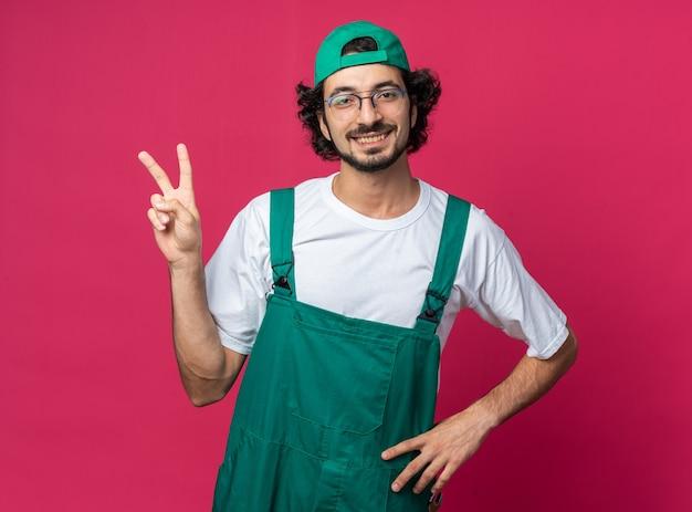 모자를 쓴 제복을 입은 웃고 있는 젊은 건축업자가 엉덩이에 손을 얹는 평화 제스처를 보여줍니다.