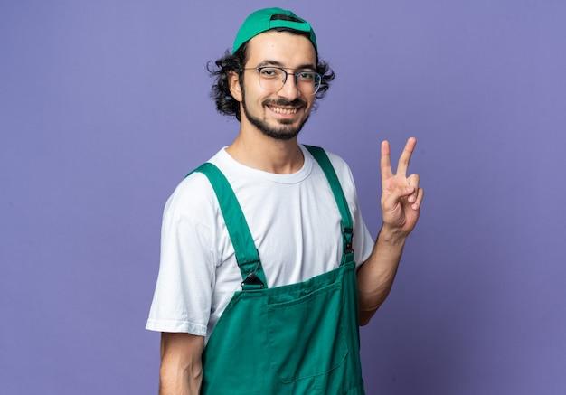 평화 제스처를 보여주는 모자와 유니폼을 입고 웃는 젊은 빌더 남자