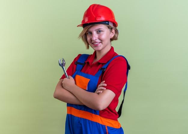 オリーブグリーンの壁に分離されたオープンエンドレンチを保持している制服を着た若いビルダーの女性の笑顔