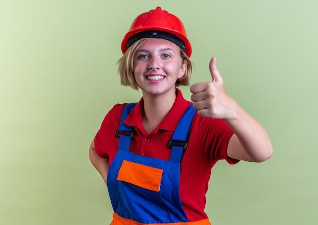 オリーブグリーンの壁に分離された親指を示す制服を着た若いビルダーの女性の笑顔