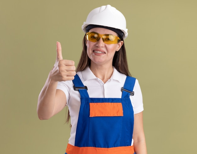 Sorridente giovane donna costruttore in uniforme e occhiali che mostra pollice in alto isolato su parete verde oliva