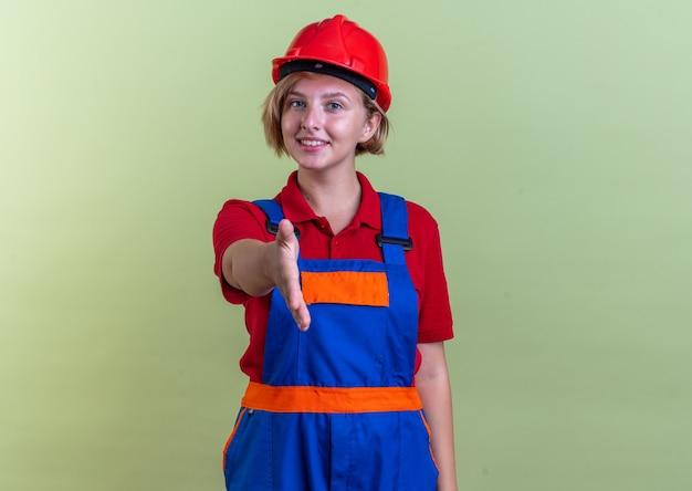 Sorridente giovane donna costruttore in uniforme tenendo fuori la mano nella parte anteriore isolata sulla parete verde oliva