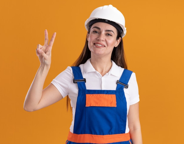 Smiling young builder woman in uniform showing peace gesture isolated on orange wall