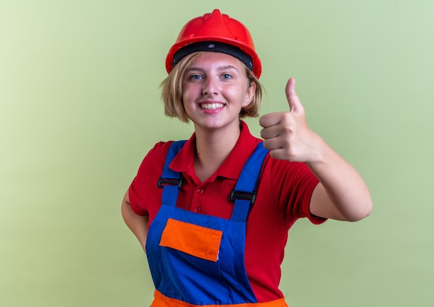 Sorridente giovane donna del costruttore in uniforme che mostra pollice in su isolato sulla parete verde oliva