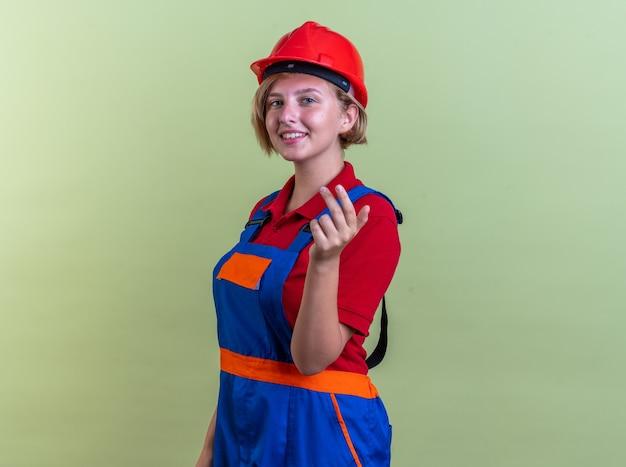 Sorridente giovane donna costruttore in uniforme che mostra due isolati su parete verde oliva