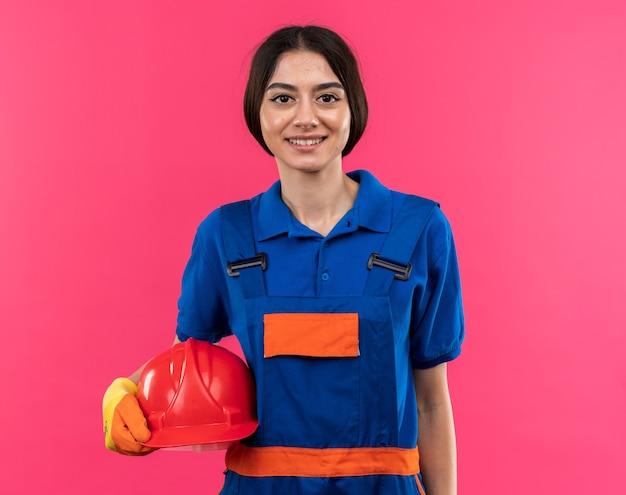 Sorridente giovane donna costruttore in uniforme che indossa guanti che tengono il casco di sicurezza