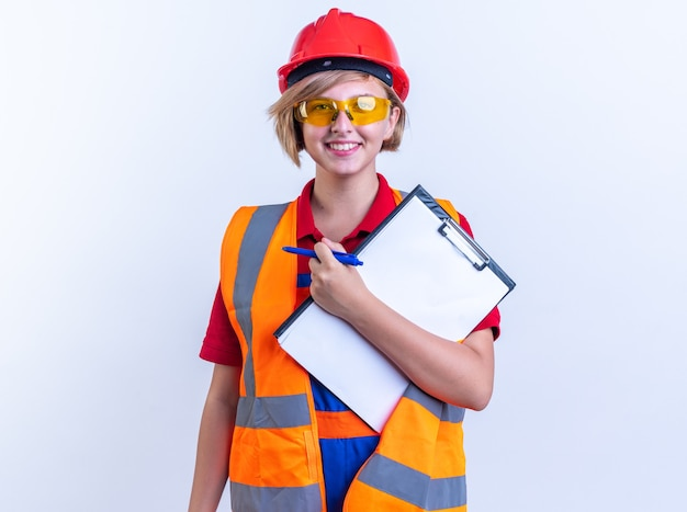 Sorridente giovane donna builder in uniforme con gli occhiali che tengono appunti con penna isolata sul muro bianco