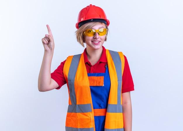 Sorridente giovane donna costruttore in uniforme con gli occhiali punta verso l'alto isolato sul muro bianco