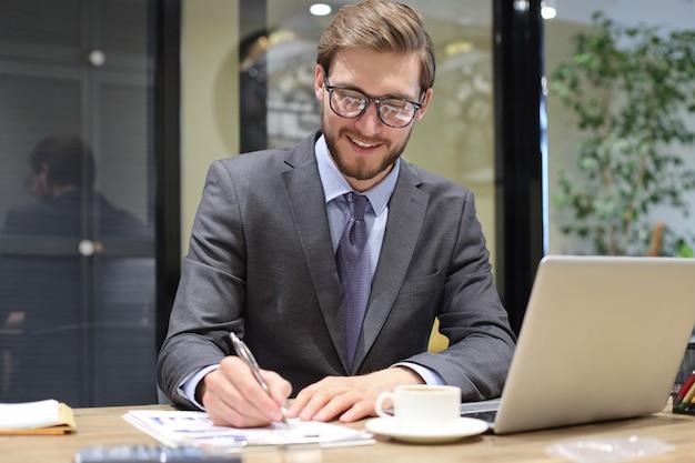 Улыбающийся молодой деловой человек что-то записывает во время работы в современном офисе.