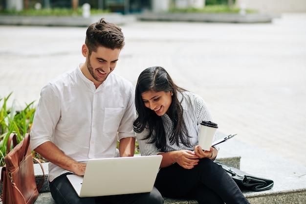 노트북 화면에 프로젝트 프리젠 테이션을 논의하는 젊은 비즈니스 사람들이 웃고