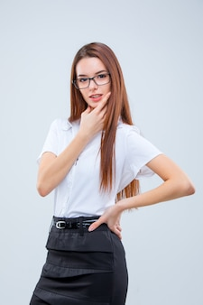 Smiling young business woman on gray wall