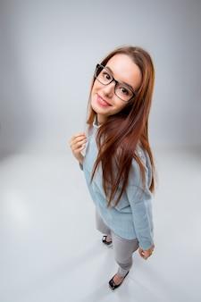 La giovane donna sorridente di affari sul muro grigio
