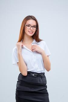 회색 배경에 안경에 웃는 젊은 비즈니스 우먼