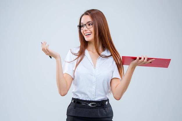 Улыбающаяся молодая деловая женщина в очках с ручкой и планшетом для заметок на сером фоне