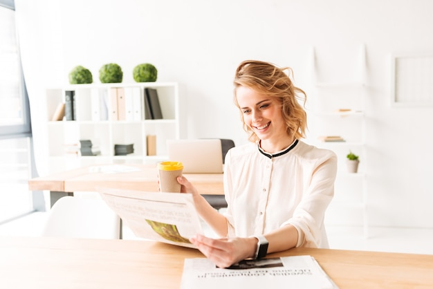 Улыбающиеся молодые деловая женщина, читая газету, пить кофе.
