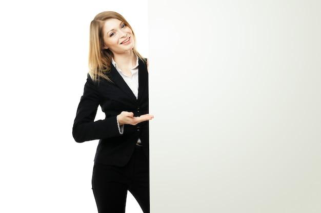 Улыбающаяся молодая деловая женщина, показывающая пустую вывеску, на белом фоне изолирована