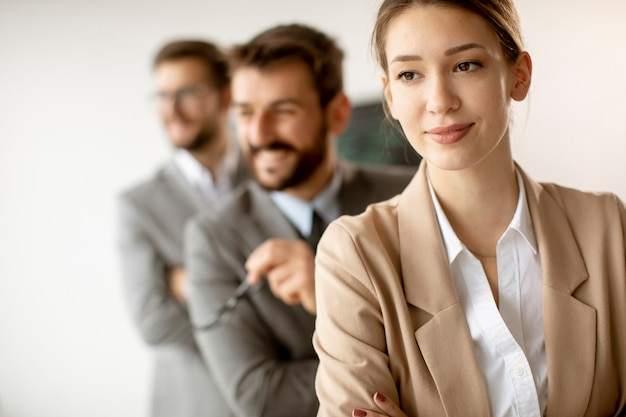 Smiling young business woman standing with group of corporate colleagues in a row together at the office