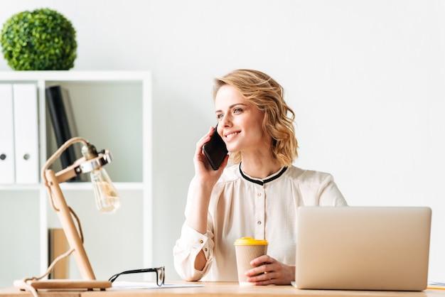 携帯電話で話している笑顔の若いビジネス女性。