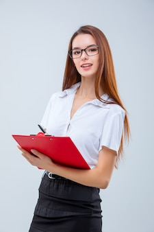The smiling young business woman with pen and tablet for notes on gray