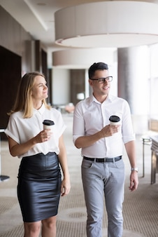 Smiling young businessman and businesswoman walking with coffee in office.