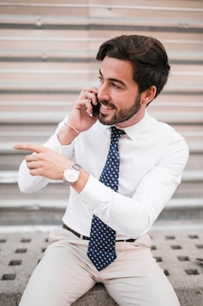Smiling young businessman gesturing while talking on smartphone