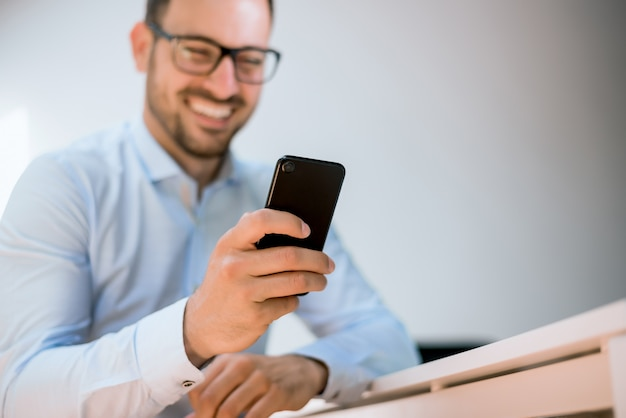 Smiling young businessman in glasses using his martphone at workplce.