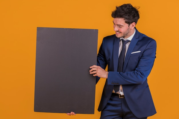 A smiling young businessman holding blank black placard against an orange backdrop