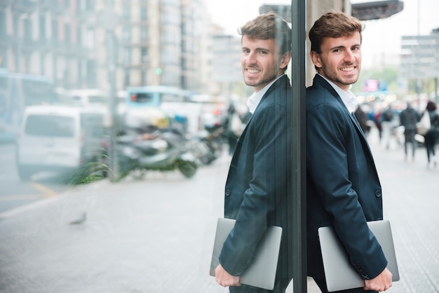 Smiling young businessman holding mobile phone in hand leaning on glass wall
