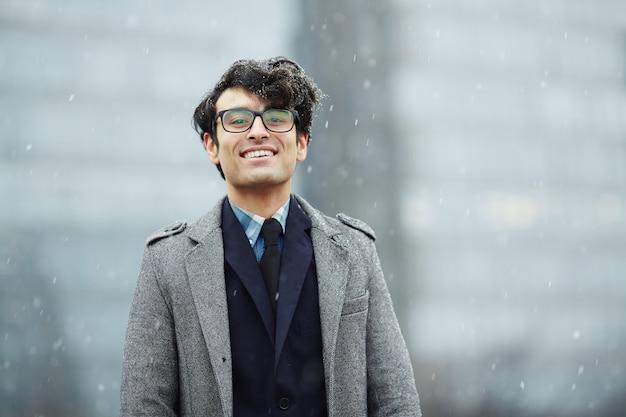 雪の中で笑顔の青年実業家